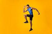 Handsome black sportsman walks highly lifting knees