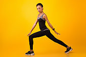 African Woman Doing Lunge Exercise Stertching Legs Over Yellow Background
