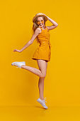 Carefree Youth. Positive Teen Girl Jumping Over Yellow Studio Background