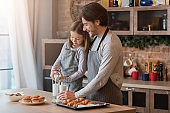 Little girl pouring milk to glasses, having bite with dad in kitchen