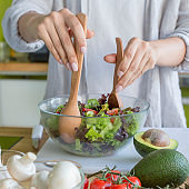 Housewife making a salad and mixing it with wooden spoons