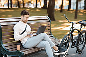 Work during break outdoors. Attractive guy sits on bench, types at laptop with coffee and bike