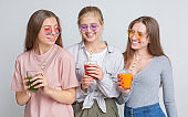 Three girlfriends drinking homemade detox smoothie and juice