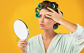 Unhappy Housewife Touching Face Frowning Looking In Mirror, Studio Shot