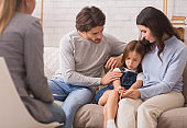 Worried parents comforting their little daughter at psychologist consultation