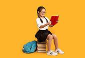 Cheerful Asian Schoolgirl Reading Sitting On Book Stack In Studio