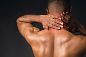 Shirtless black man suffering from pain in neck