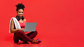 Smiling sporty athletic woman using laptop over red background