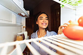 Young girl opening her fridge at home, view from inside