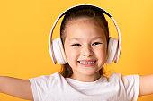Smiling asian girl enjoying music using headset