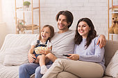 Family Of Three Relaxing At Home, Watching TV And Eating Popcorn