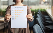 Blurred female holding paper sheet with five star rating