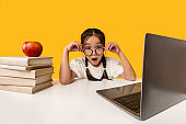 Amazed Schoolgirl Looking At Camera Sitting At Laptop, Yellow Background