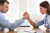 Businessman And Businesswoman Arm Wrestling Sitting At Desk In Office