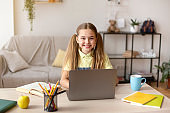 Girl sitting at table, using laptop for e-learning