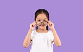 Asian Little Girl Looking At Camera Above Glasses, Studio Shot