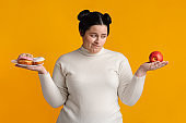 Hungry Obese Girl On Diet Making Choice Between Donuts And Apple