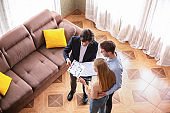 Above view of real estate agent showing house plan to young customers indoors
