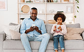 Gadget overuse problem. Senior African American man and granddaughter with smartphones at home