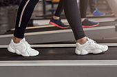 Cardio exercises. Unrecognizable woman on treadmill in gym, closeup
