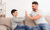 Father and son giving high five to each other at home