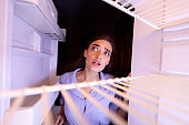 Young woman looking at empty shelves of her refrigerator