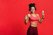 Joyful afro fitness girl enjoying music during exercising