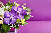 Beautiful bouquet of flowers in lilac basket on purple background with copy space. Orchids, lilies, chamomiles floral floristic composition. Greeting card for romantic date, valentine day, 8 March