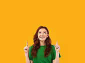 Cheerful Red-Haired Girl Pointing Fingers Up At Copyspace, Studio Shot
