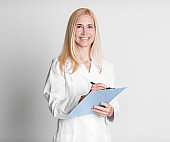 Middle aged woman holding folder writing diagnosis