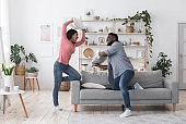 Playful african american couple fighting by pillows, fooling together at home