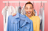 Portrait of cheerful lady showing clothes standing near rack