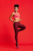 Cheerful fitness girl exercising over red background
