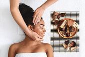 Peaceful african american woman enjoying facial massage at spa