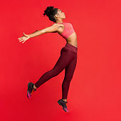 Flexible athletic girl jumping up, stretching her body