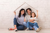 Happy Parents And Little Daughter Sitting On Floor Under Symbolic Roof