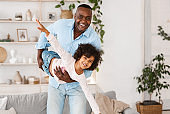 Family playtime. Happy African American grandfather playing silly game with his granddaughter at home, blank space