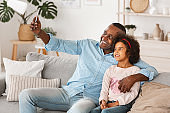 Home leisure. African American grandfather with adorable grandkid taking selfie together on cozy sofa indoors