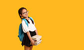 Discontented Asian School Girl Carrying Heavy Books Over Yellow Background