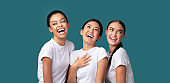 Three Happy Diverse Girls Laughing Standing Over Turquoise Background, Panorama
