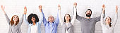 Group of happy diverce people holding hands, raising arms up, panorama