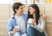 Happy millennial couple resting on kitchen floor with hot cups