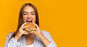 Young Lady Biting Burger Enjoying Junk Food, Panorama, Studio Shot
