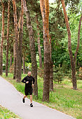 Male runner jogging on road, exercising outdoor