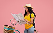 Lovely African American woman with bicycle looking at map over pink studio background