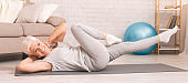 Active senior woman exercising on floor at home, panorama