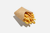 French fries and fast food takeaway in menu during pandemic. Fried potatoes in ecological paper packaging with shadow