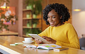 Cheerful african girl using social media on digital tablet