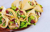 Baked tortillas cones with lettuce and meat on white background.
