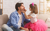 Cute little girl putting make up on her father